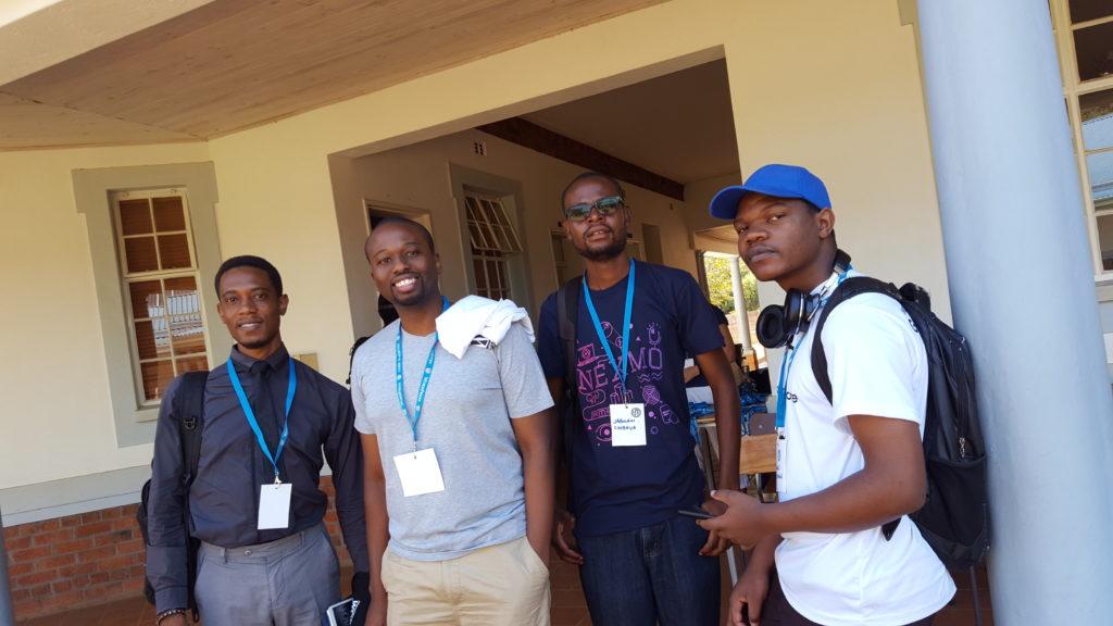 4 junge Teilnehmer posieren für ein Foto; dunkle Haut, von leger bis formell gekleidet, einer mit Base-Cap, alle mit WordCamp-Namensschildern um den Hals