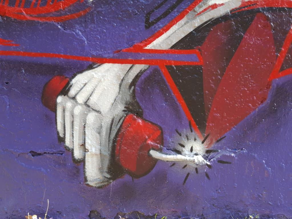 Graffiti: hand holding burning stick of dynamite