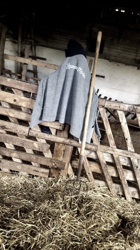 Goat stable scenery: fork leaned at fence, hoodie and cap hanging next to it, straw on the ground