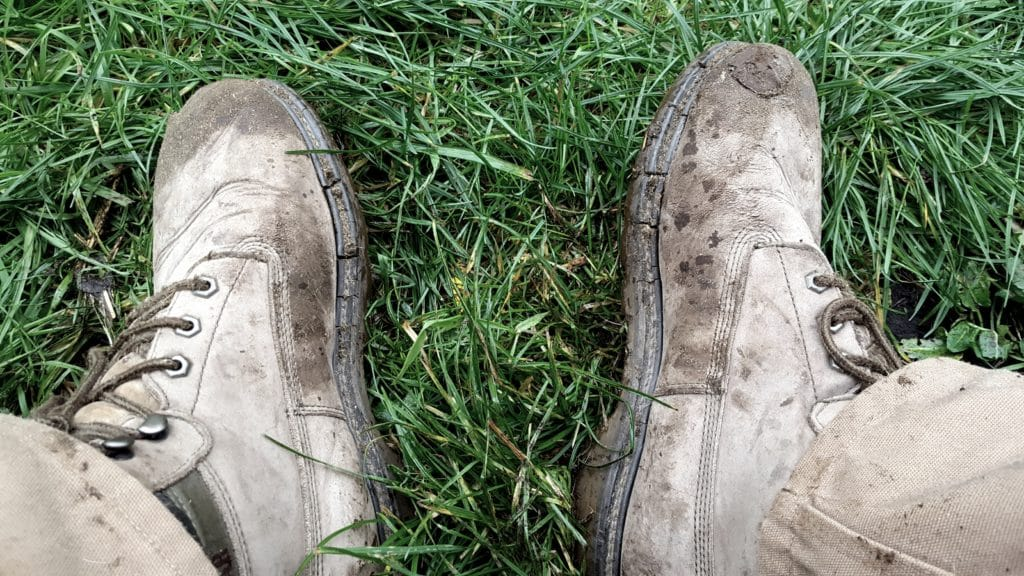 Muddy working boots on grass